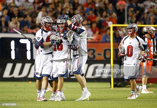 Ryan Tucker of the Boston Cannons celebrates with teammates after scoring during their MLL game against the Denver Outlaws at Sports Authority Field...