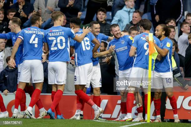Ryan Tunnicliffe of Portsmouth FC celebraytes with team-mates after he scores a goal to make it 1-0 during the Sky Bet Championship match between...