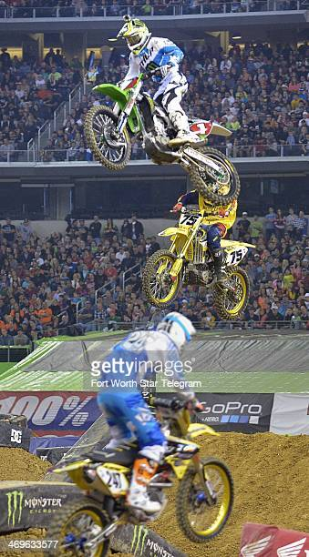 Ryan Villopoto and Joshua Hill soar over a jump during a 450SX heat in the Monster Energy AMA Supercross at ATT Stadium in Arlington Texas on...