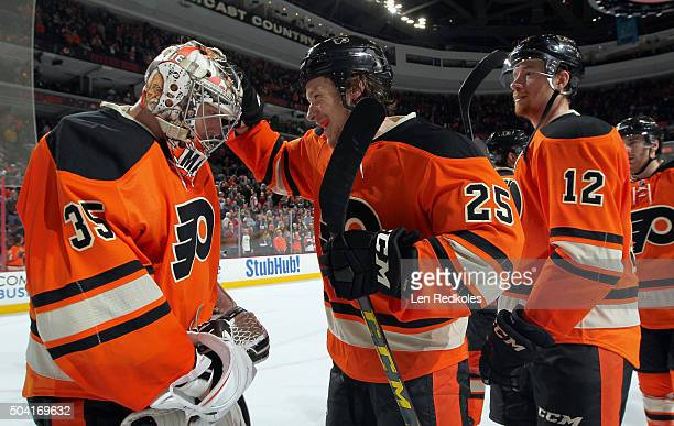 Ryan White and Michael Raffl of the Philadelphia Flyers celebrate with goaltender Steve Mason after defeating the New York Islanders 40 on January 9...