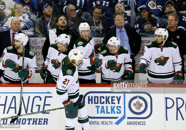 Ryan White of the Minnesota Wild celebrates his second period goal against the Winnipeg Jets with teammates at the bench at the MTS Centre on...