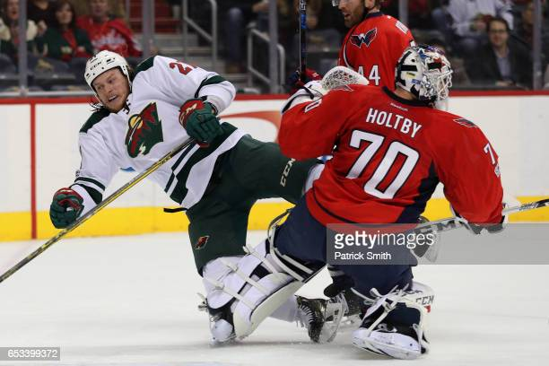 Ryan White of the Minnesota Wild collides with goalie Braden Holtby of the Washington Capitals during the first period at Verizon Center on March 14...