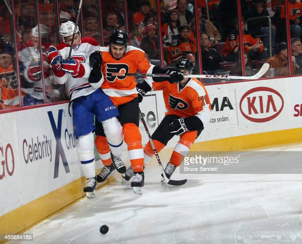 Ryan White of the Montreal Canadiens is hit into the boards by Zac Rinaldo of the Philadelphia Flyers during the second period at the Wells Fargo...