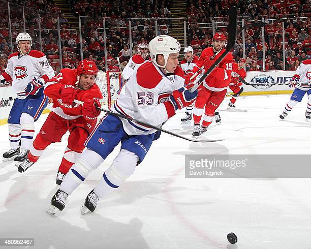 Ryan White of the Montreal Canadiens skates with the puck as David Legwand of the Detroit Red Wings puts a stick on him during an NHL game on March...
