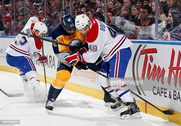 Ryan White of the Montreal Canadiens takes control of the puck as teammate Michael Bournival battles with Alexander Sulzer of the Buffalo Sabres at...