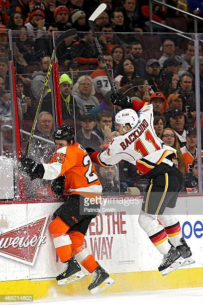 Ryan White of the Philadelphia Flyers and Mikael Backlund of the Calgary Flames crash into the boards at Wells Fargo Center on March 3 2015 in...