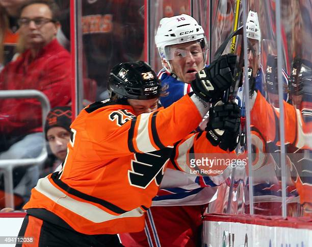 Ryan White of the Philadelphia Flyers checks JT Miller of the New York Rangers into the boards on October 24 2015 at the Wells Fargo Center in...