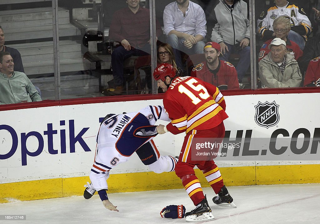 Ryan Whitney #6 of the Edmonton Oilers has his jersey pulled over his head during a fight with Tim Jackman #15 of the Calgary Flames at Scotiabank Saddledome on April 3, 2013 in Calgary, Alberta, Canada.