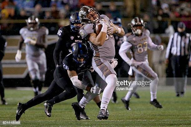Ryan Williamson of the Buffalo Bulls tackles Donnie Ernsberger of the Western Michigan Broncos in the third quarter at Waldo Stadium on November 19,...
