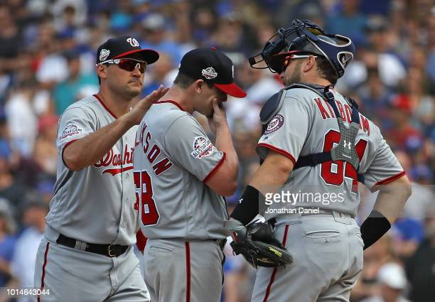 Ryan Zimmerman and Spencer Kieboom of the Washington Nationals console starting pitcher Jeremy Hellickson before he's taken out of the game against...