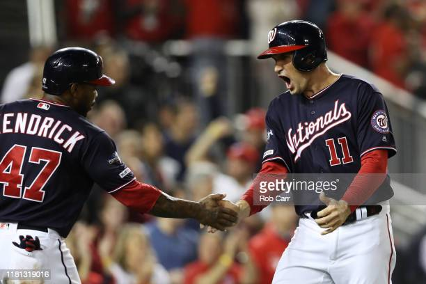 Ryan Zimmerman celebrates scoring with Howie Kendrick of the Washington Nationals in the first inning against the St Louis Cardinals during game four...