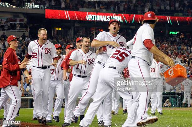 Ryan Zimmerman of the Washington Nationals celebrates with teammates after scoring the game winning run in the tenth inning against the New York Mets...