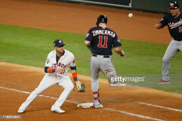 Ryan Zimmerman of the Washington Nationals reaches first base safely against Yuli Gurriel of the Houston Astros on a throw from Alex Bregman during...