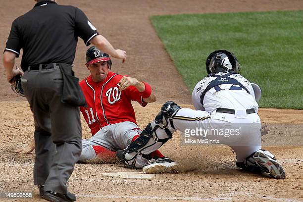 Ryan Zimmerman of the Washington Nationals slides into home plate avoiding the tag from Martin Maldonado of the Milwaukee Brewers putting the...