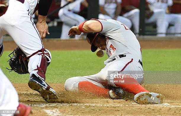 Ryan Zimmerman of the Washington Nationals slides safely into home plate as the throw hits him in the face during the second inning against the...