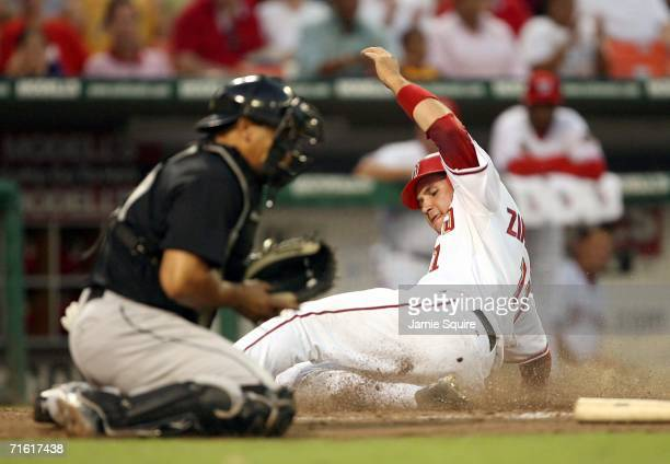Ryan Zimmerman of the Washington Nationals slides safely into home to score on a Alex Escobar sacrifice to right field for the Nationals third run...