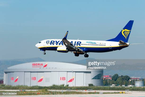 A Ryanair Boeing 737800 aircraft lands next to a hangar of Spanish airline Iberia at Barcelona's 'El Prat' airport on September 28 2018 Ryanair...