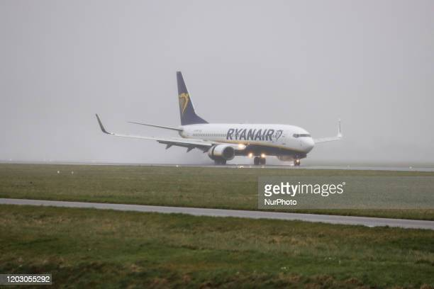 A Ryanair Boeing 737800 or 737NG aircraft as seen landing at Polderbaan runway and taxiing during bad weather with a storm with rain high wind...