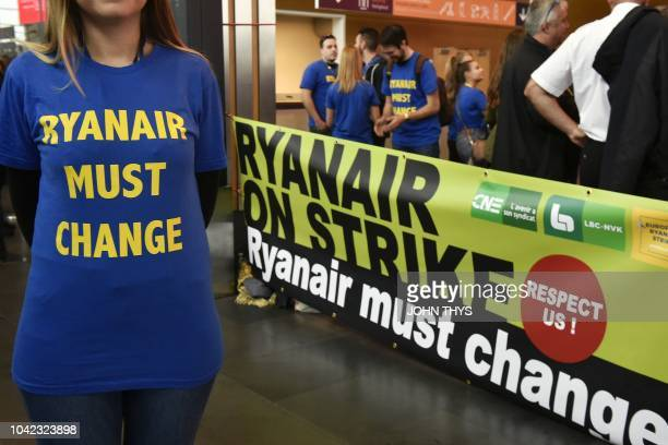 A Ryanair employee wearing a tshirt reading 'Ryanair must change' stands past a banner during what could be the biggest strike in the airline's...