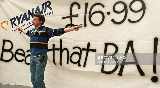 Ryanair's chief executive Michael O'Leary gestures in front of a banner the company erected outside of rival British Airways' travel shop 03...