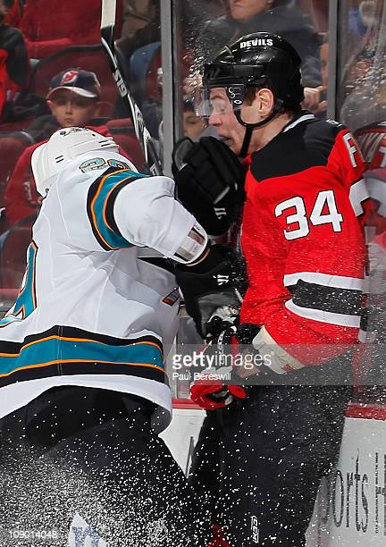 Ryane Clowe of the San Jose Sharks checks Mark Fayne of the New Jersey Devils during the first period of an NHL hockey game on February 11 2011 at...