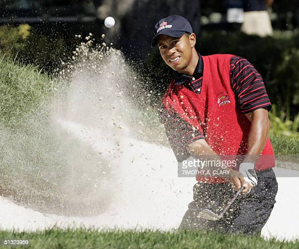 Ryder Cup golfer Tiger Woods blasts out of the sand trap on the third hole during his singles match agasint Paul Casey 19 September 2004 at Oakland...