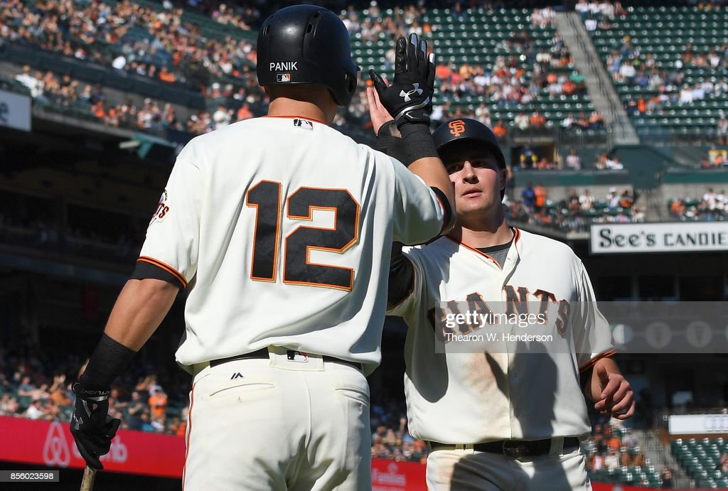 Ryder Jones #63 of the San Francisco Giants is congratulated by Joe Panik after Jones scored against the San Diego Padres in the bottom of the seventh inning at AT&T Park on September 30, 2017 in San Francisco, California.