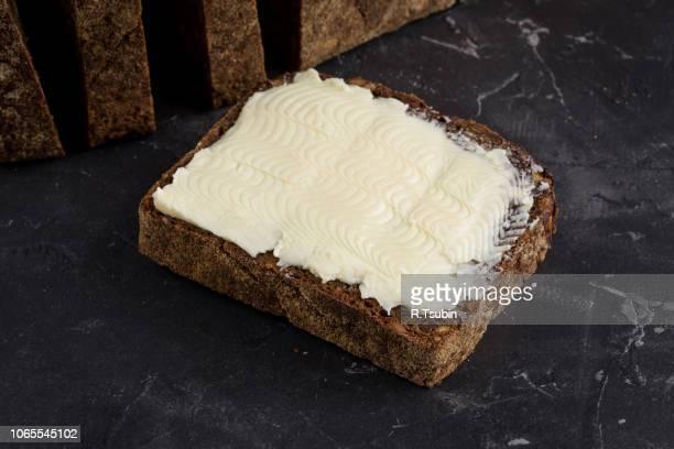 rye black bread with seeds and butter on dark board background - crosta di formaggio foto e immagini stock