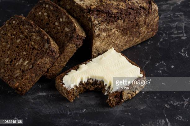 Rye black bread with seeds and butter on dark board background