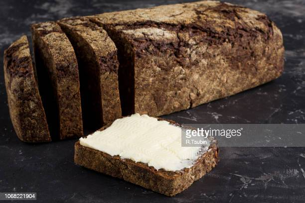 rye black bread with seeds and butter on dark board background - margarine stock pictures, royalty-free photos & images