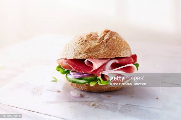 a rye bread role with ham, vegetables and lettuce - wax paper stock photos and pictures