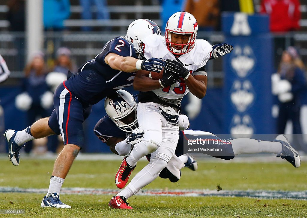 Ryheem Malone #13 of the SMU Mustangs is tackled by Graham Stewart #2 of the Connecticut Huskies in the first quarter during the game at Rentschler Field on December 6, 2014 in East Hartford, Connecticut.