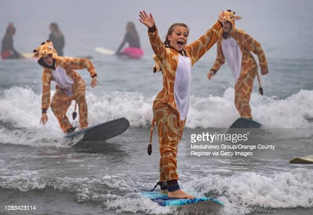 Rylee Lyng leads a tower of giraffes through the surf during Blackies 17th Annual Halloween Surf event in Newport Beach on Saturday, October 31, 2020.