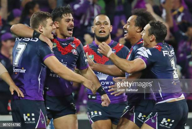 Ryley Jacks of the Melbourne Storm is congratulated by his Billy Slater of the Melbourne Storm and his teammates after scoring the first try during...
