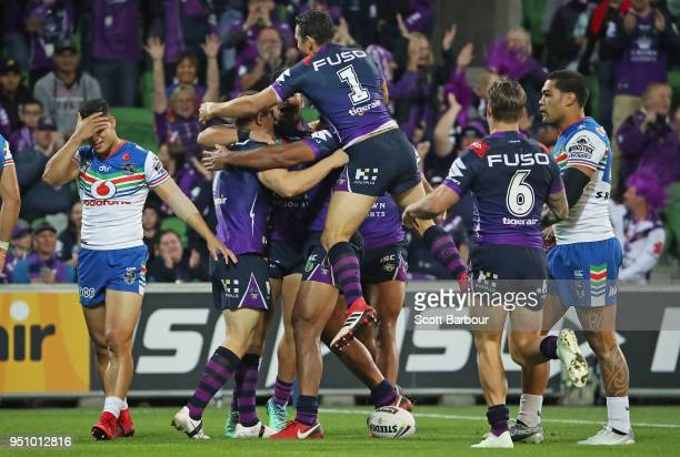 Ryley Jacks of the Melbourne Storm is congratulated by his teammates after scoring the first try during the round eight NRL match between the...