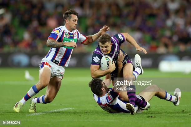 Ryley Jacks of the Storm runs with the ball as he is tackled by the Knights defence during the round six NRL match between the Melbourne Storm and...