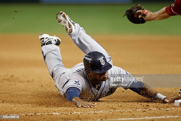 Rymer Liriano of the San Diego Padres dives back to first base to avoid being doubled up on a deep fly ball during the seventh inning of a MLB game...