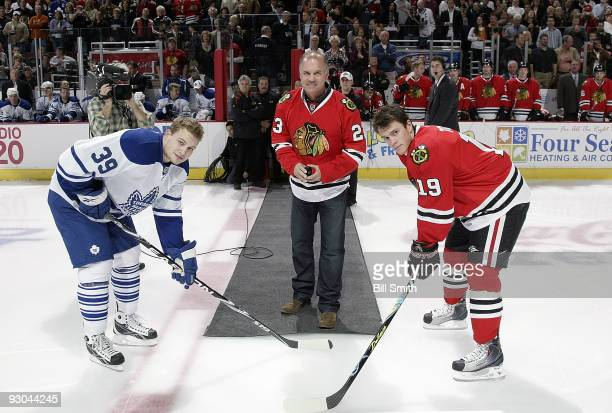 Ryne Sandberg, former second baseman for the Chicago Cubs drops the puck with Jonathan Toews of the Chicago Blackhawks and John Mitchell of the...