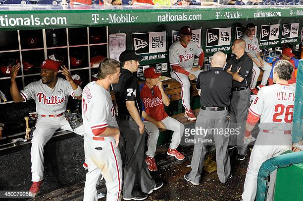 Ryne Sandberg of the Philadelphia Phillies talks with the umpire crew during a rain delay in the game against the Washington Nationals at Nationals...