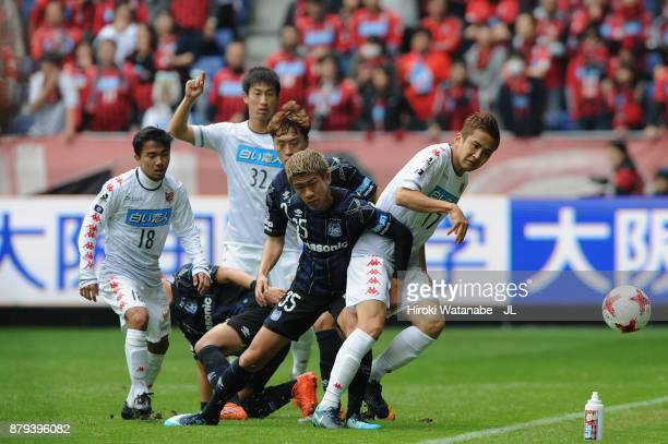 Ryo Hatsuse of Gamba Osaka and Junichi Inamoto of Consadole Sapporo compete for the ball during the JLeague J1 match between Gamba Osaka and...