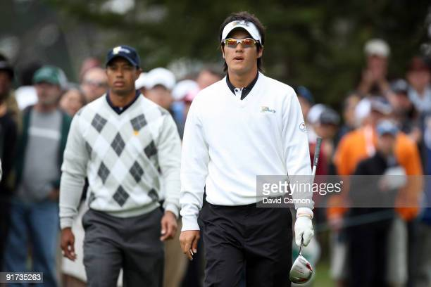 Ryo Ishikawa of Japan and the International Team walks from the 6th tee followed by Tiger Woods of the USA Team during the Day Three Afternoon...