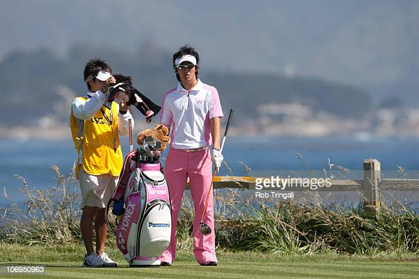 Ryo Ishikawa of Japan looks on with his caddie Hiroyuki Kato on the 18th hole during the first round of the 110th U.S. Open at Pebble Beach Golf...