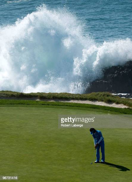 Ryo Ishikawa of Japan makes a putt on the seventh green as waves come crashing on the rocks during the third round of the ATT Pebble Beach National...