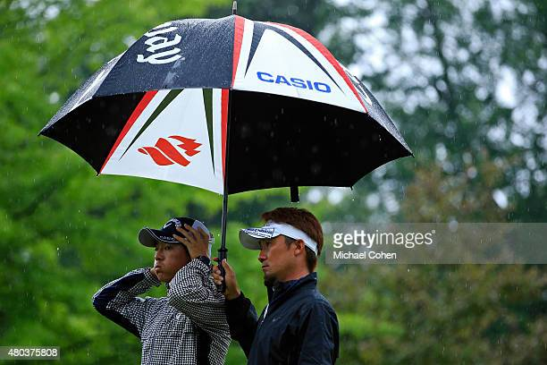 Ryo Ishikawa of Japan prepares to tee off on the first hole while his caddie Yoshi Sato holds an umbrella during the third round of the John Deere...