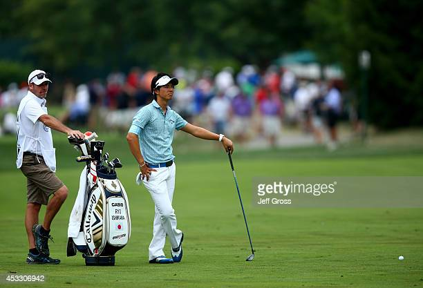 Ryo Ishikawa of Japan waits to hit his second shot on the tenth hole alongside caddie Simon Clarke during the first round of the 96th PGA...