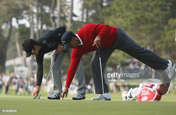 Ryo Ishikawa of the International Team and Tiger Woods of the USA Team mark their balls during the Day One Foursome Matches of The Presidents Cup at...