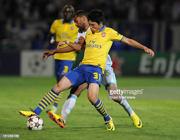 Ryo Miyaichi of Arsenal challenged by Saber Khalifa of Marseille during the match at Stade Velodrome on September 18 2013 in Marseille France