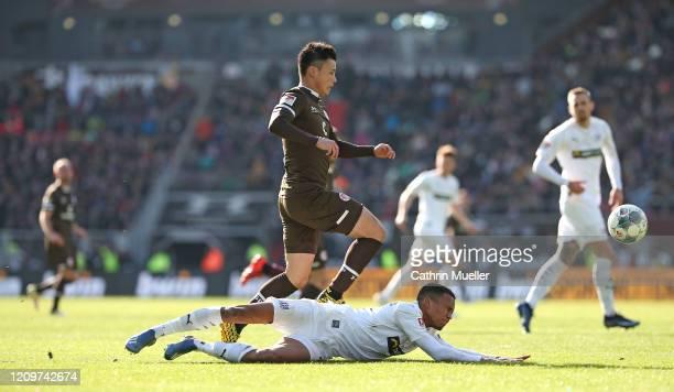 Ryo Miyaichi of FC St. Pauli and Felix Agu of VfL Osnabrueck battle for the ball during the Second Bundesliga match between FC St. Pauli and VfL...