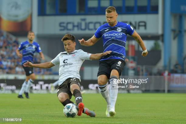 Ryo Miyaichi of St Pauli and Florian Hartherz of Bielefeld fight for the ball during the Second Bundesliga match between DSC Arminia Bielefeld and FC...
