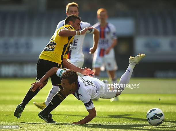 Ryo Nagai of Perth trips over Emmanuel Muscat of the Phoenix during the round 19 ALeague match between the Wellington Phoenix and the Perth Glory at...